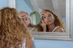 A jovem mulher lindo está arrancando as sobrancelhas foto de stock royalty free