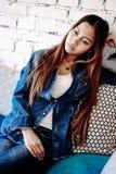 Jovem mulher lindo na calças de ganga que refrigera em um clube do VIP Fotografia de Stock