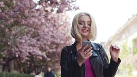 A jovem mulher lindo que anda abaixo da cereja floresceu aleia e surfando o Internet, sorrindo felizmente para vídeos de arquivo