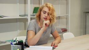 Jovem mulher lindo que faz anotações ao estudar vídeos de arquivo