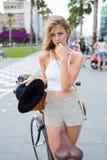 Jovem mulher lindo tentador que está com bicicleta clássica fora fotografia de stock