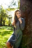 A jovem mulher lindo veste o vestido cinzento, com cabelo no levantamento do vento Imagens de Stock