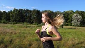 A jovem mulher loura bonita, alta, atlética, menina, na parte superior e no short faz um movimento, corre ao longo do trajeto do  video estoque