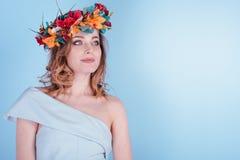 A jovem mulher loura bonita com flores envolve-se, cabelo encaracolado longo e composição no fundo azul imagem de stock