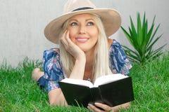 A jovem mulher loura bonita em um chapéu está encontrando-se na grama e está lendo-se um livro fotografia de stock