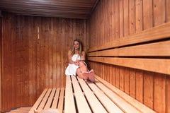 Jovem mulher loura bonita que relaxa uma sauna imagem de stock