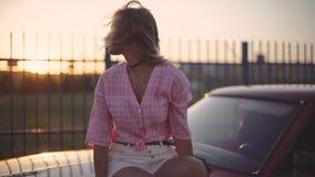 A jovem mulher loura bonita senta-se na capa de seu carro no por do sol filme