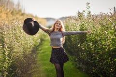 Jovem mulher loura feliz na estrada rural fotos de stock royalty free