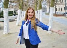 Jovem mulher loura feliz no parque com sorriso enigmático imagens de stock