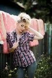 Jovem mulher loura na camisa e na calças de ganga do vaqueiro Fotografia de Stock Royalty Free