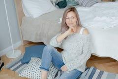 A jovem mulher loura no pulôver cinzento está perto da cama imagem de stock royalty free