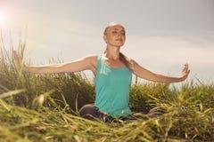 Jovem mulher loura que medita sobre a natureza com os olhos fechados Fotografia de Stock Royalty Free