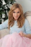 A jovem mulher loura senta-se perto da árvore de Natal Fotografia de Stock Royalty Free