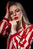 Jovem mulher luxuosa nos vidros que levantam com o estúdio azul e vermelho l Imagem de Stock