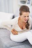 Jovem mulher má de sentimento que senta-se no sofá Imagens de Stock
