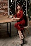 A jovem mulher magnífica no vestido vermelho luxuoso e na joia preciosa está sentando-se em uma cadeira em um apartamento luxuoso imagem de stock