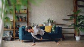 A jovem mulher magro está fazendo a sequência de asanas da ioga do hatha apenas em casa que aprecia o treinamento e a solidão pes video estoque
