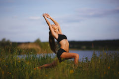 Jovem mulher magro que faz a ioga exterior Pose do guerreiro Fotos de Stock Royalty Free