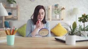 A jovem mulher mancha o batom rachado dos bordos que senta-se na frente do espelho vídeos de arquivo