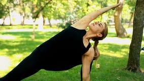 Jovem mulher meados de do tiro que faz a ioga no parque vídeos de arquivo
