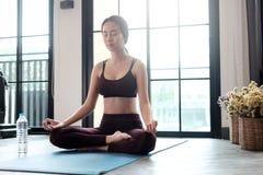 A jovem mulher medita ao praticar a ioga em sua sala Fotografia de Stock Royalty Free