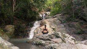 A jovem mulher medita na cachoeira video estoque
