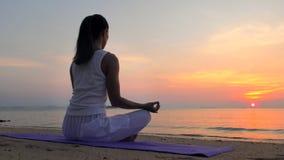 A jovem mulher medita no mar do por do sol video estoque