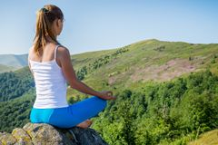 A jovem mulher medita sobre a parte superior da montanha imagem de stock royalty free