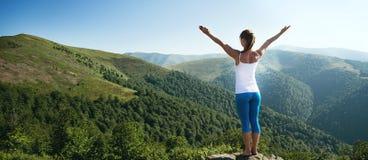 A jovem mulher medita sobre a parte superior da montanha imagem de stock