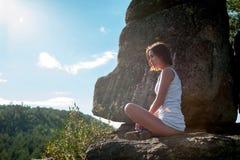 A jovem mulher medita sobre a parte superior da montanha no tempo do nascer do sol Fotos de Stock