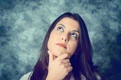 Jovem mulher mediterrânea com cabelo marrom longo que pensa fotografia de stock