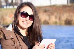 Jovem mulher/menina que usa o assento exterior da tabuleta no banco próximo perto Foto de Stock Royalty Free