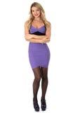 Jovem mulher Mini Dress With Arms Folded curto roxo apertado vestindo de sorriso e saltos altos Fotografia de Stock Royalty Free