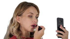 Jovem mulher ? moda bonita que aplica o batom vermelho nos bordos e que olha a tela do telefone no fundo branco imagens de stock royalty free
