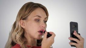 Jovem mulher ? moda bonita que aplica o batom vermelho nos bordos e que olha a tela do telefone no fundo do inclina??o imagens de stock royalty free