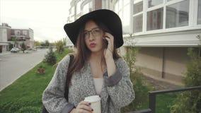 Jovem mulher moderna que ri alegremente a fala no telefone esperto da pilha móvel na cidade filme