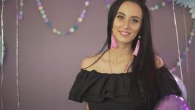 A jovem mulher moreno atrativa bonita aprecia a atmosfera da celebração do partido que sorri com os balões de ar coloridos à disp vídeos de arquivo