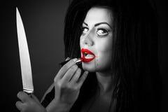 Jovem mulher moreno que aplica o batom usando a faca como um RIM Fotos de Stock Royalty Free