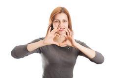 A jovem mulher mostra aos dedos o coração humano como um sinal do amor Fotografia de Stock