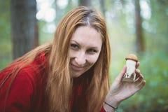 A jovem mulher mostra a cogumelos o boleto na floresta, fim acima imagem de stock royalty free