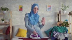 Jovem mulher muçulmana alegre na casa de linho passada hijab video estoque