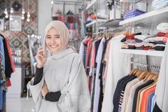 Jovem mulher muçulmana asiática que usa seu telefone esperto no st da forma Fotografia de Stock Royalty Free