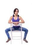 A jovem mulher muito bonita com as caudas está sentando-se nos pés da cadeira largamente isolados distante no fundo branco Fotografia de Stock