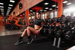 Jovem mulher muscular com o corpo bonito que faz exercícios com peso fotografia de stock royalty free