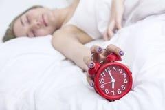 A jovem mulher não quer acordar e entregar a colocação do despertador Imagem de Stock Royalty Free