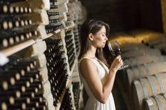 Jovem mulher na adega de vinho fotografia de stock