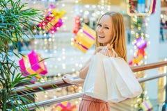 Jovem mulher na alameda do Natal com compra do Natal Bu da beleza imagem de stock