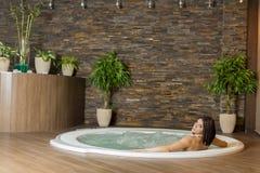 Jovem mulher na banheira de hidromassagem imagens de stock royalty free