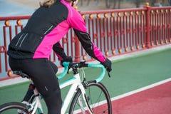 Jovem mulher na bicicleta cor-de-rosa da estrada da equitação do revestimento na linha da bicicleta da ponte em Sunny Autumn Day  fotografia de stock