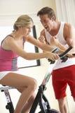 Jovem mulher na bicicleta de exercício com instrutor Fotografia de Stock Royalty Free